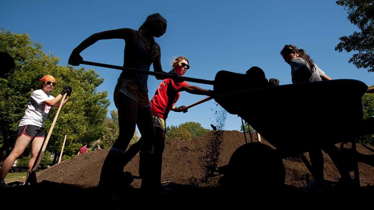 Students shovel compost to use for a sod sofa