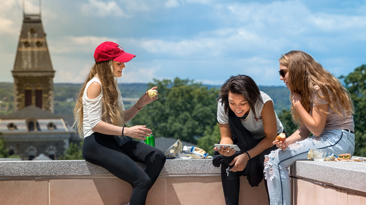 Three young women eat on a ledge overlooking campus, laughing and talking