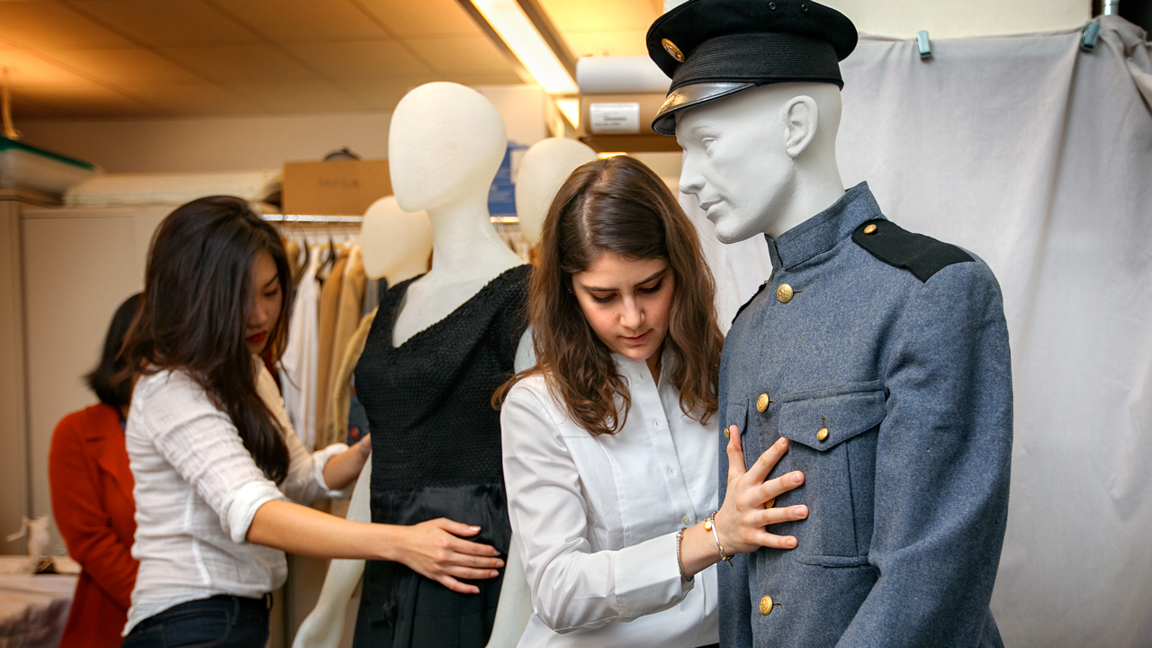 Two design students dress a mannequin with the Cornell Cadet Corps uniform in preparation for the exhibit, at the 150 Years of Cornell Fashion exhibition