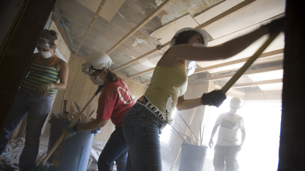 students demolishing a house with hand tools
