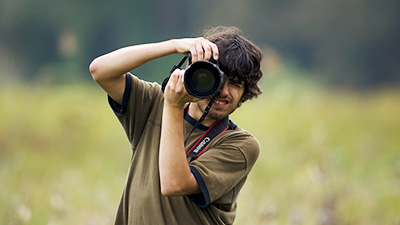 male student takes a photo in the field