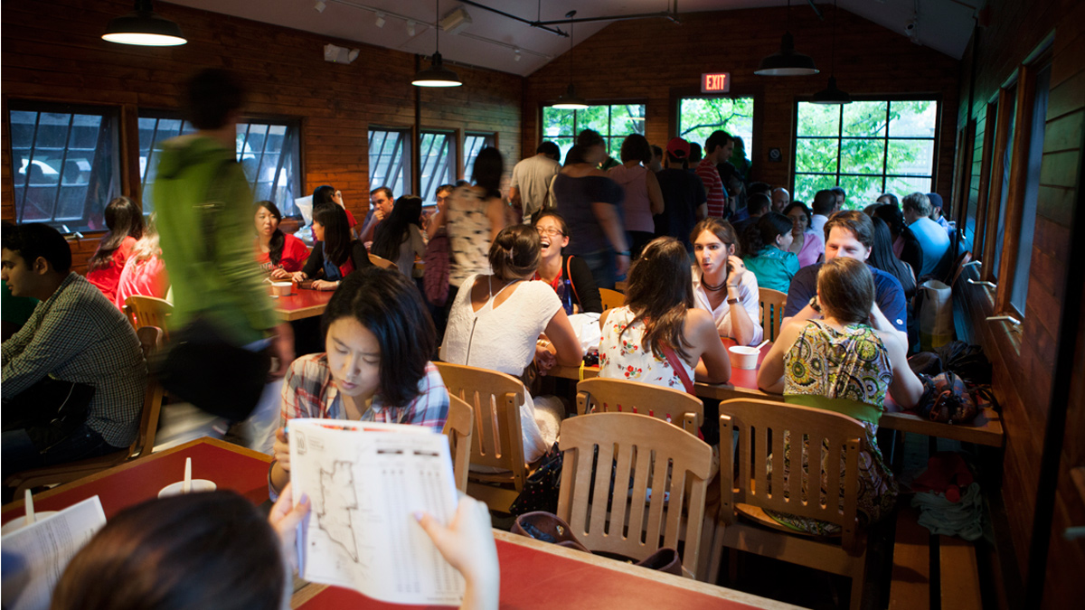 lots of students sitting at tables in the big red barn, cornell's graduate student center