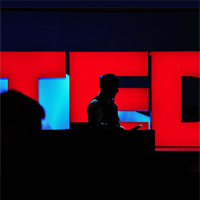 silhouette of TED lecturer in front of red TED sign