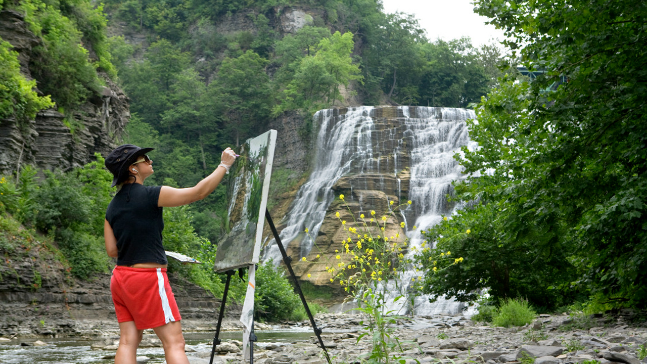 Female student with canvas and easel paints the scene at the base of a waterfall